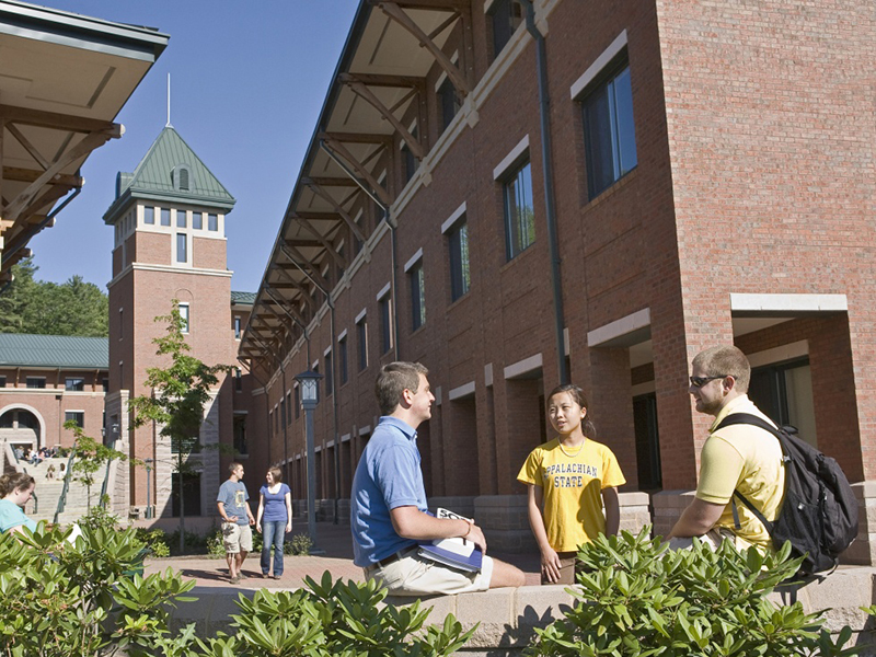 Three students talking in the courtyard of the Living Learning Center, where Watauga Residential College students live